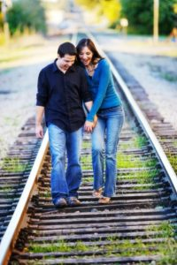couple-walking-on-railroad-tracks-image