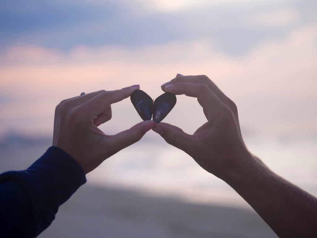 Couple making a heart with their hands asking themselves why true love is so hard to find.