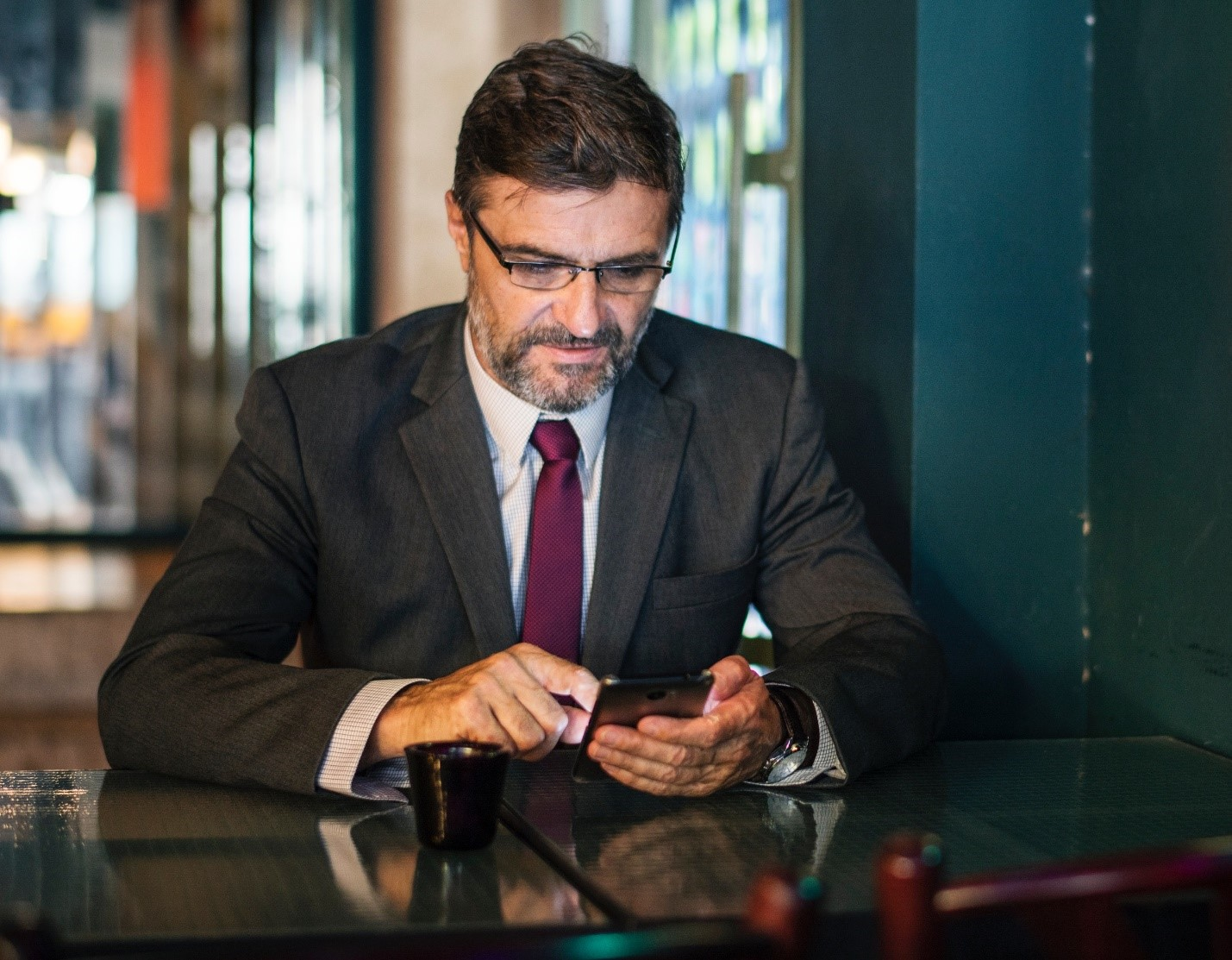 Man in suit searching his phone for advice for finding true love.