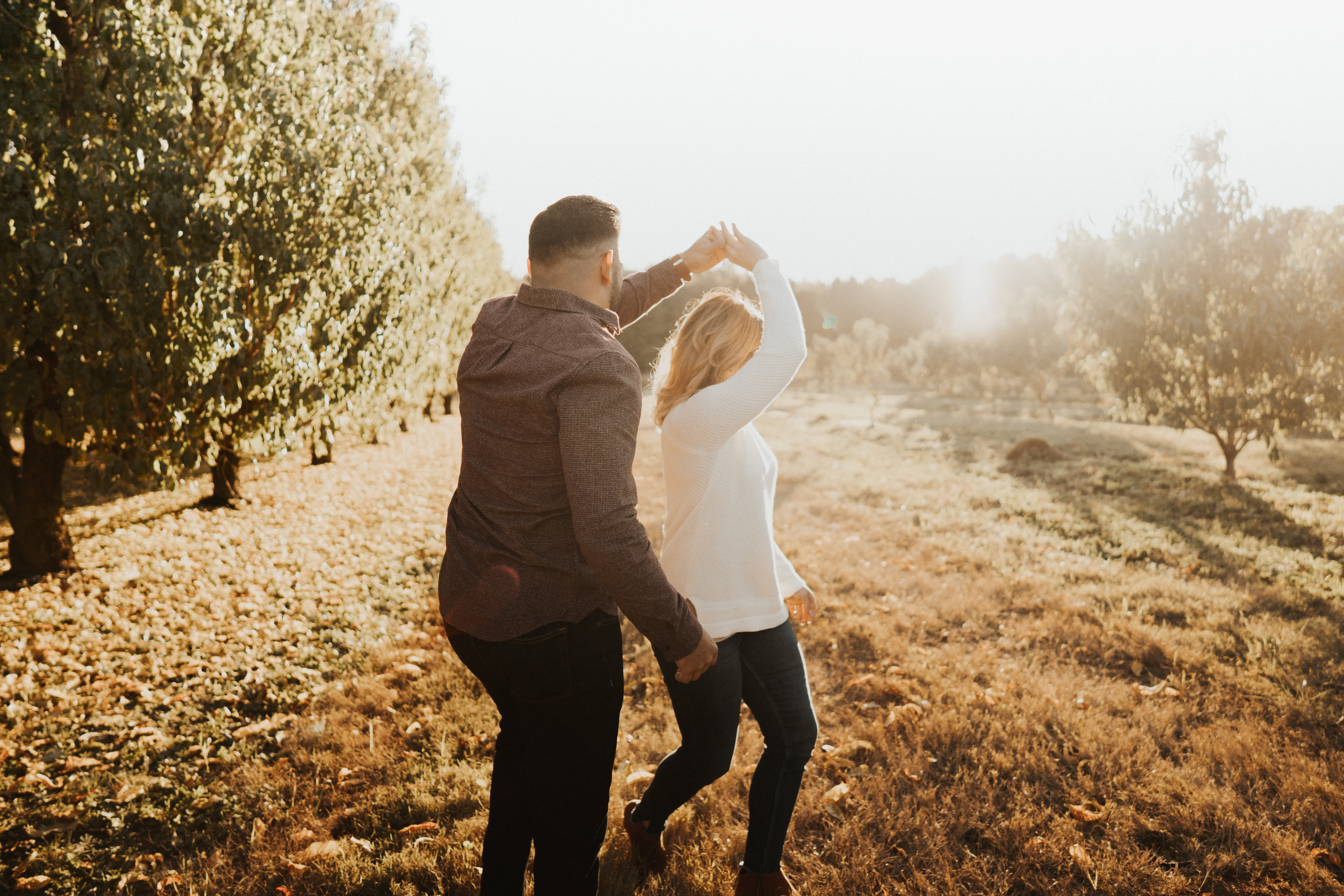 A couple happily dancing in a field after finding true love after 40.
