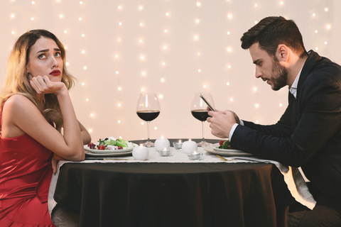 Couple at dinner who need relationship advice because they're ignoring each other.