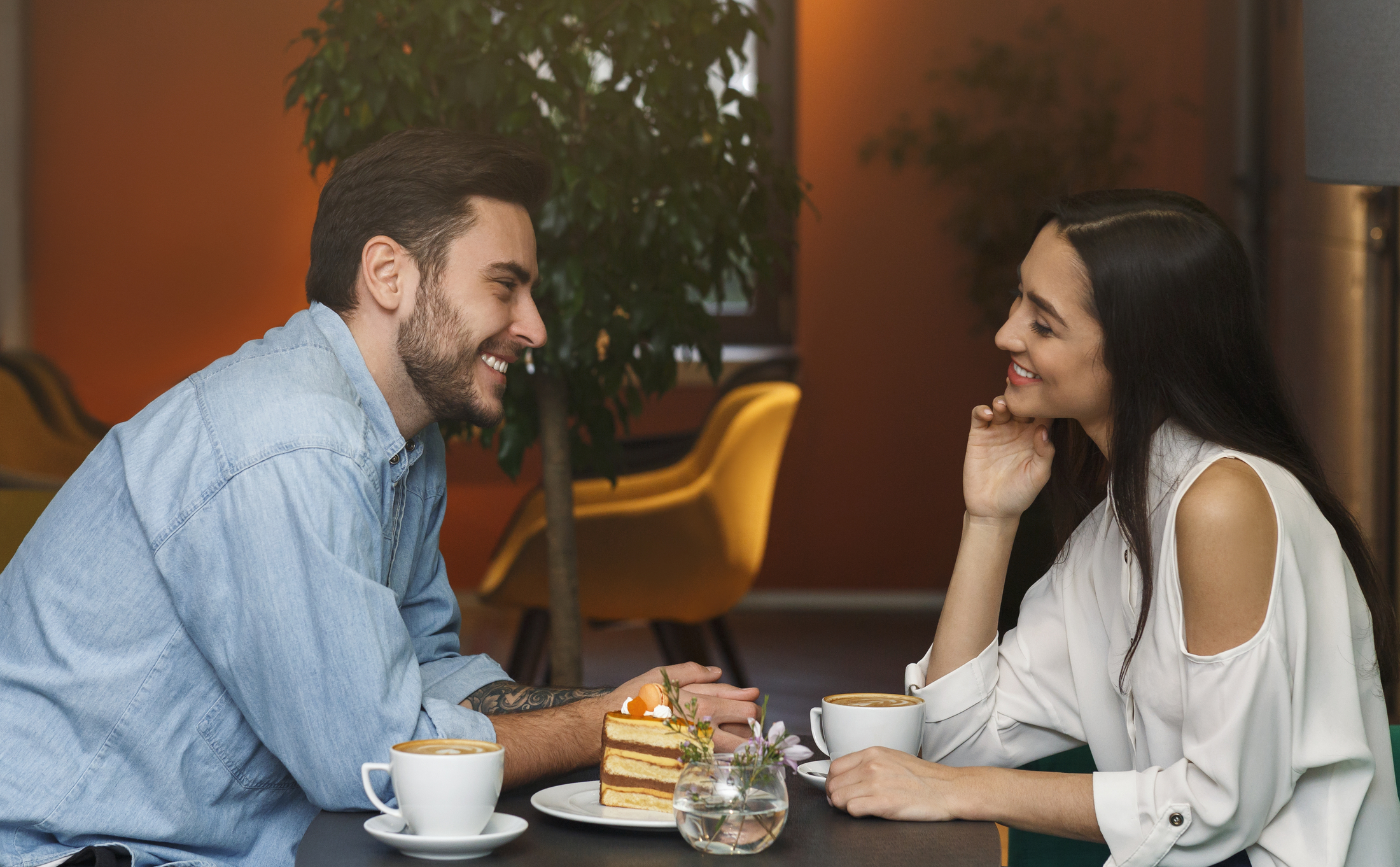 Over 35-year-old couple sitting with coffee and dessert enjoying their date.