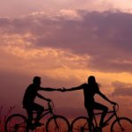 Couple riding bikes and holding hands at sunset.