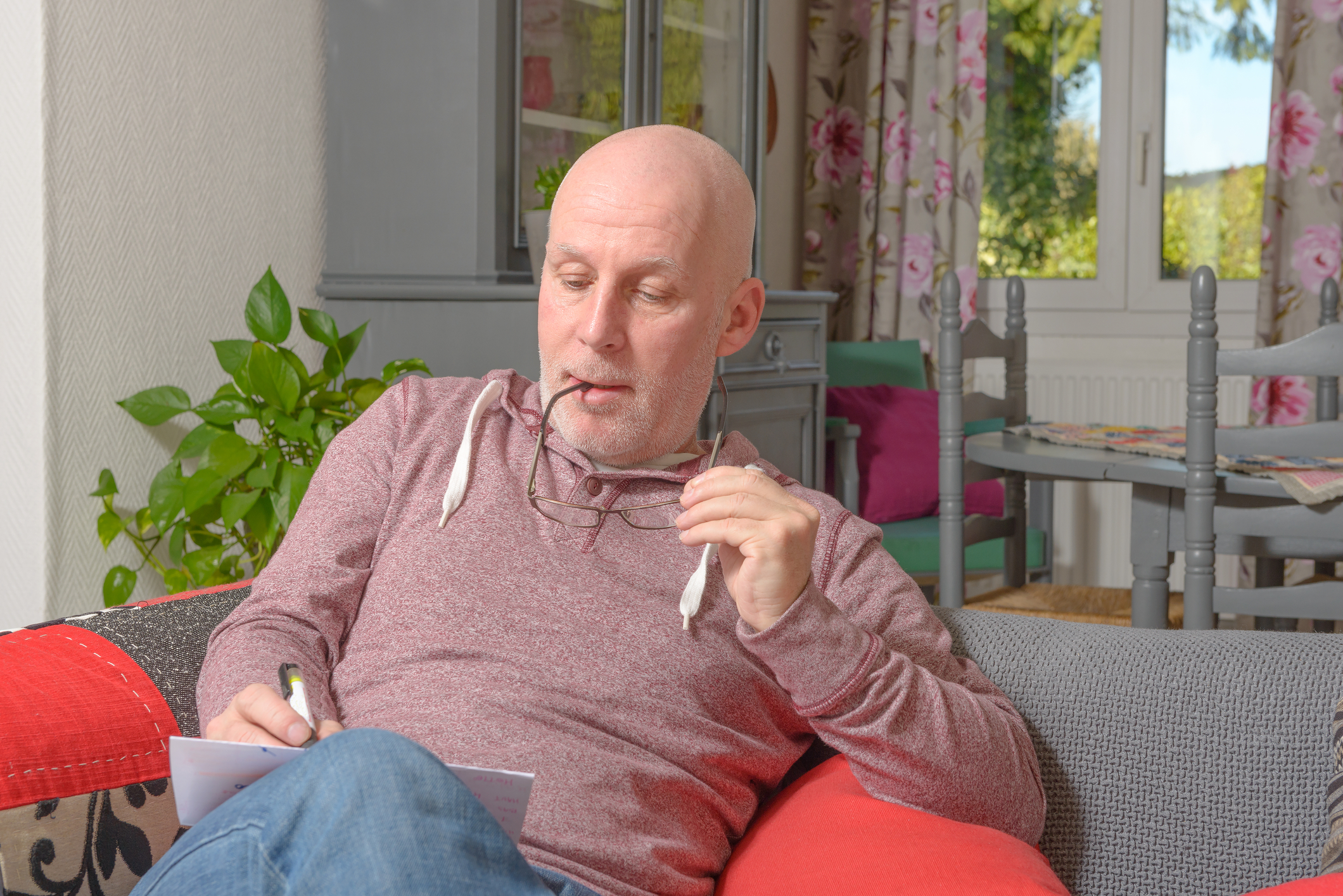Man sitting on his couch working on his dating plan for finding true love.