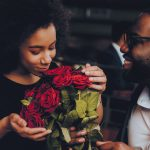 Over 40 man giving beautiful red roses to his date.