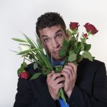 Man who is holding a bouquet of broken roses and finding true love difficult.