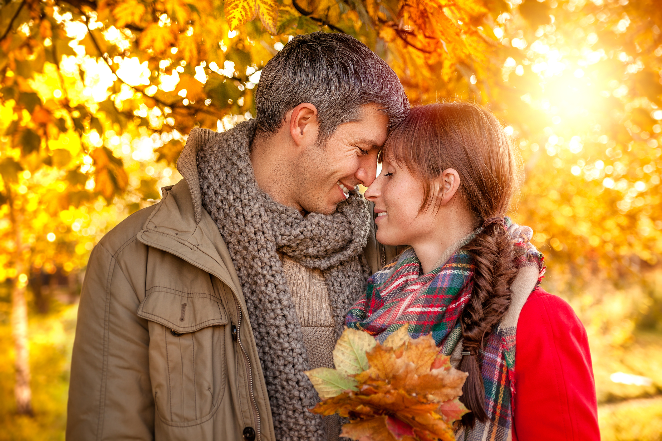 Man and woman hugging in a forest filled with fall foliage.